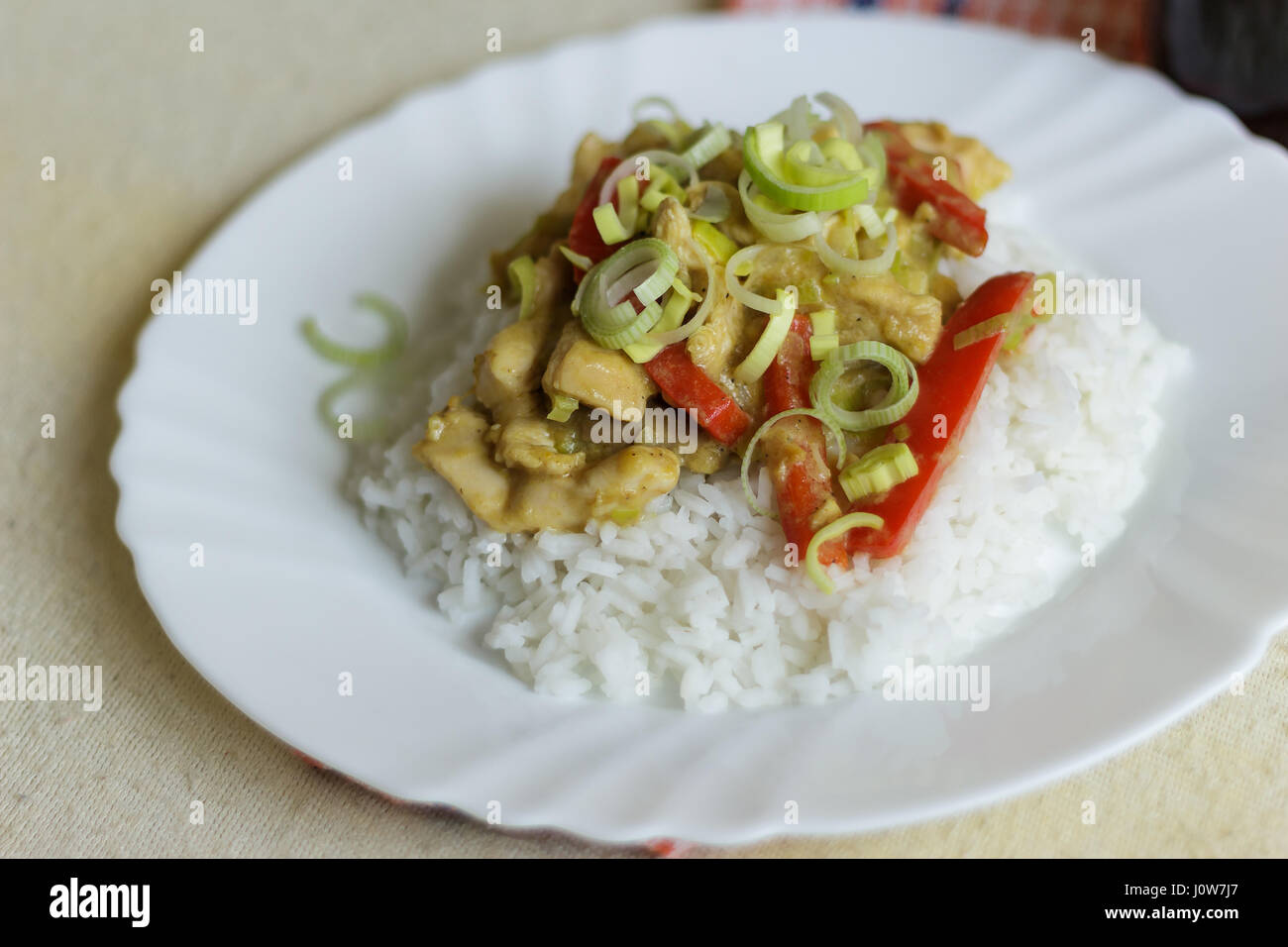 Vietnamese food - roast chicken meat with vegetables and rice on a white plate - Stock Image