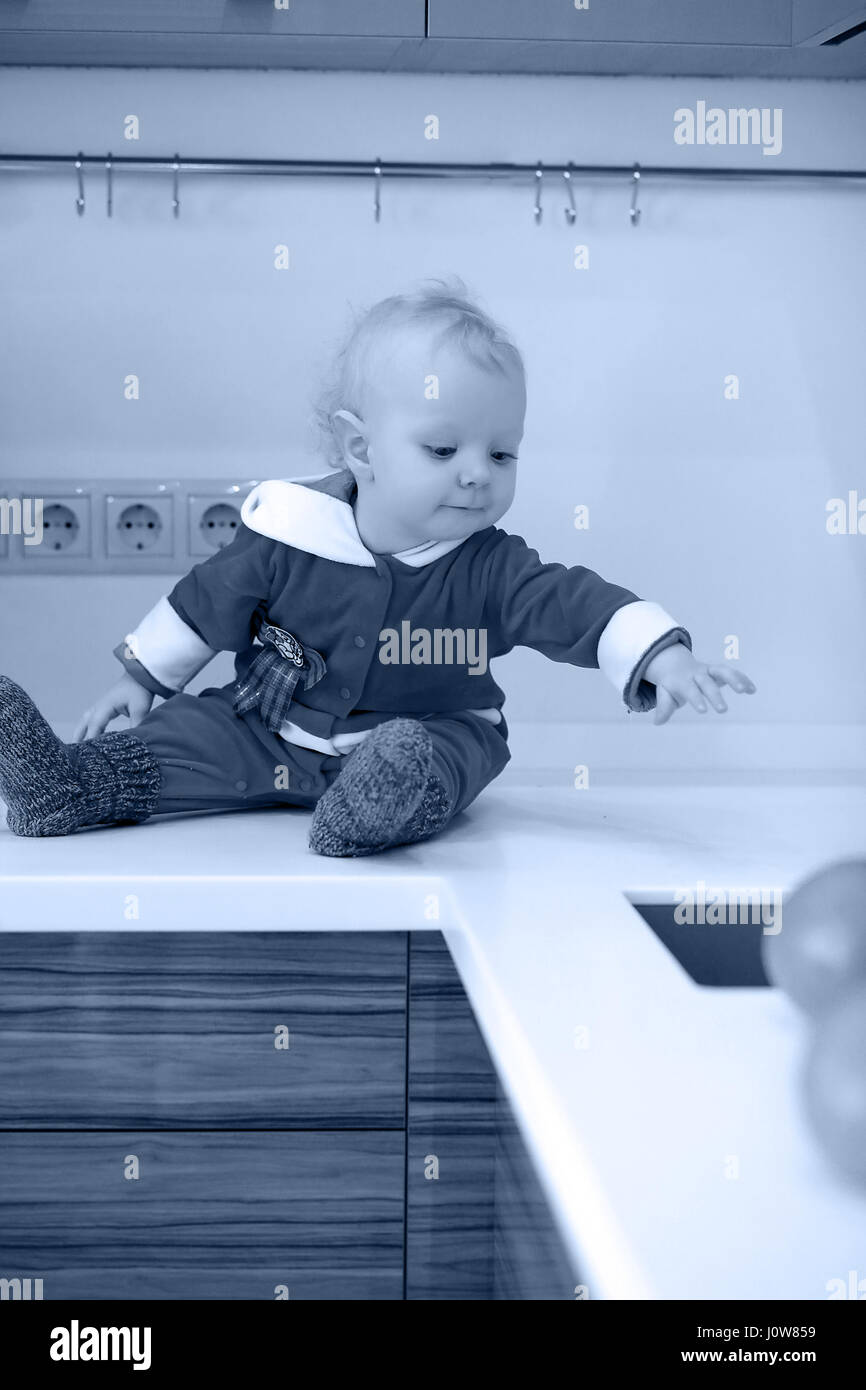 Monochrome photo of little child in the kitchen sits on a table - Stock Image