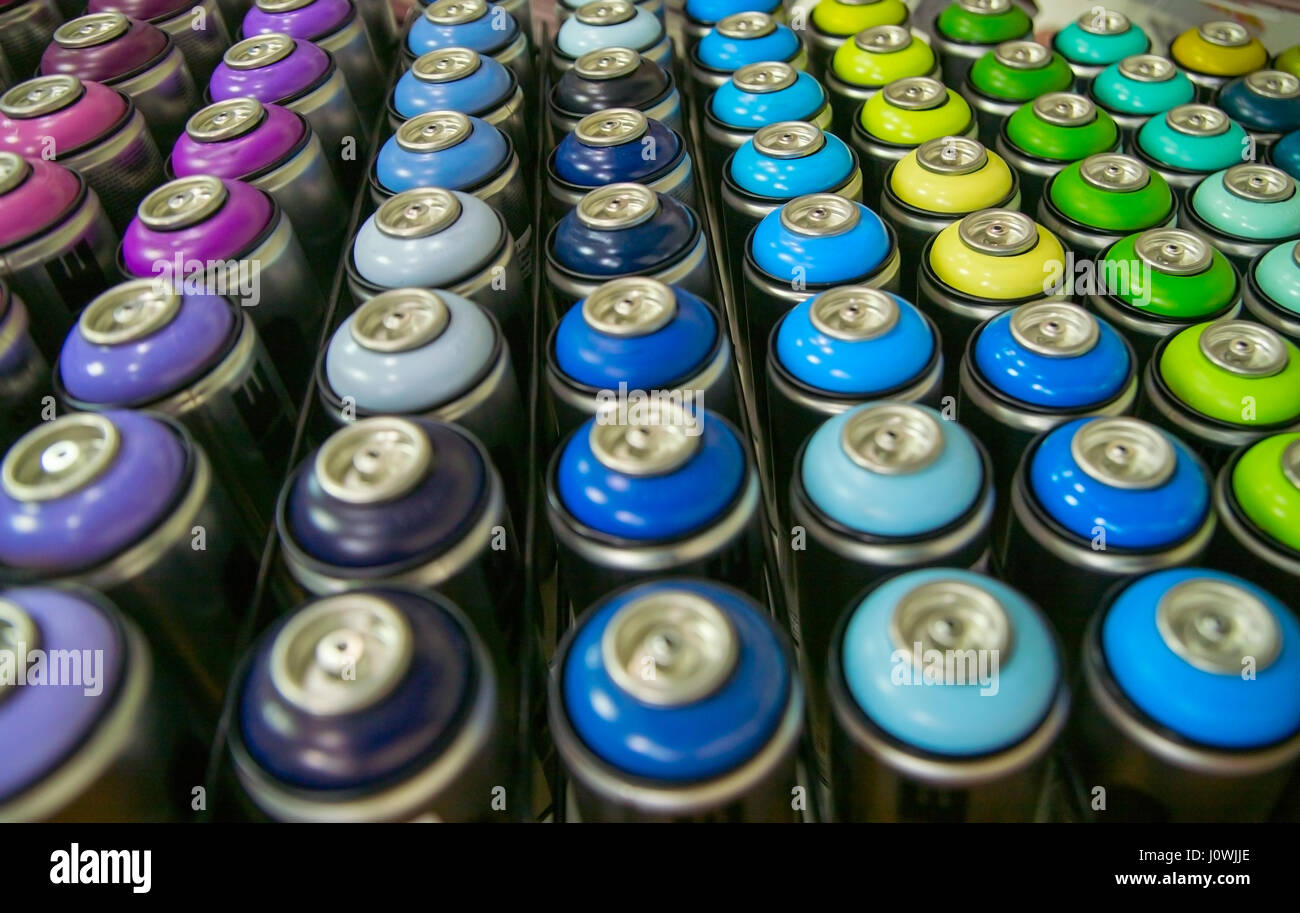 colorful cans of paint stand rows on a shelf Stock Photo