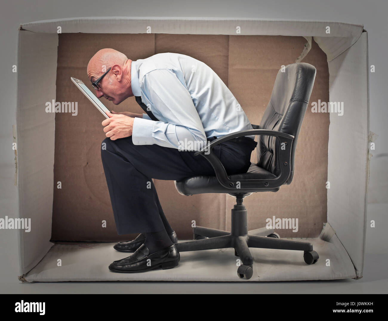 Old businessman sitting in small box - Stock Image