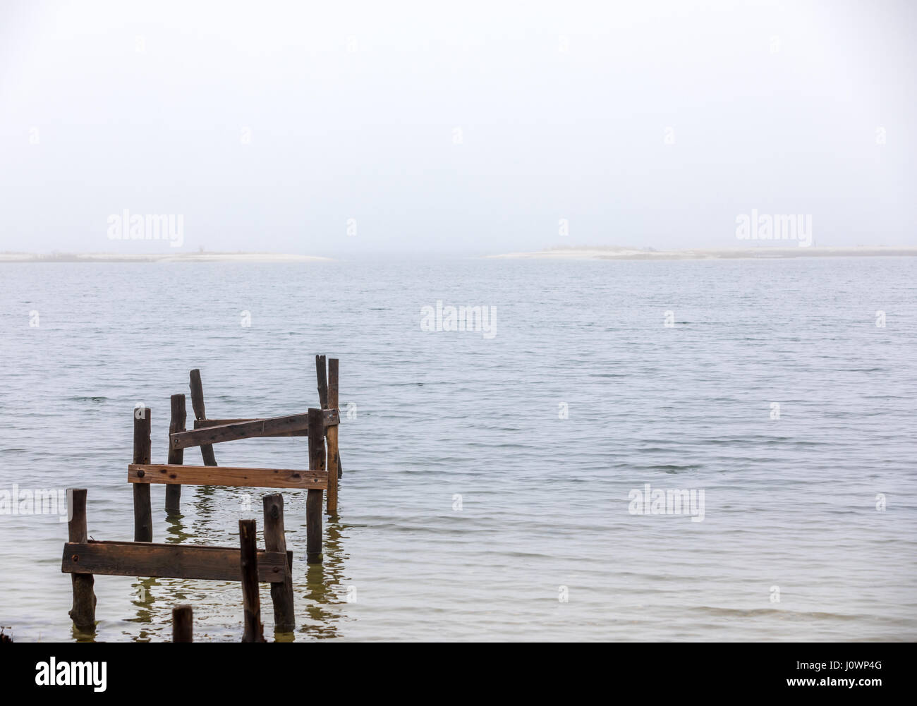 remnants of an old dock leading out into cold water on a foggy day in Hampton Bays, NY - Stock Image