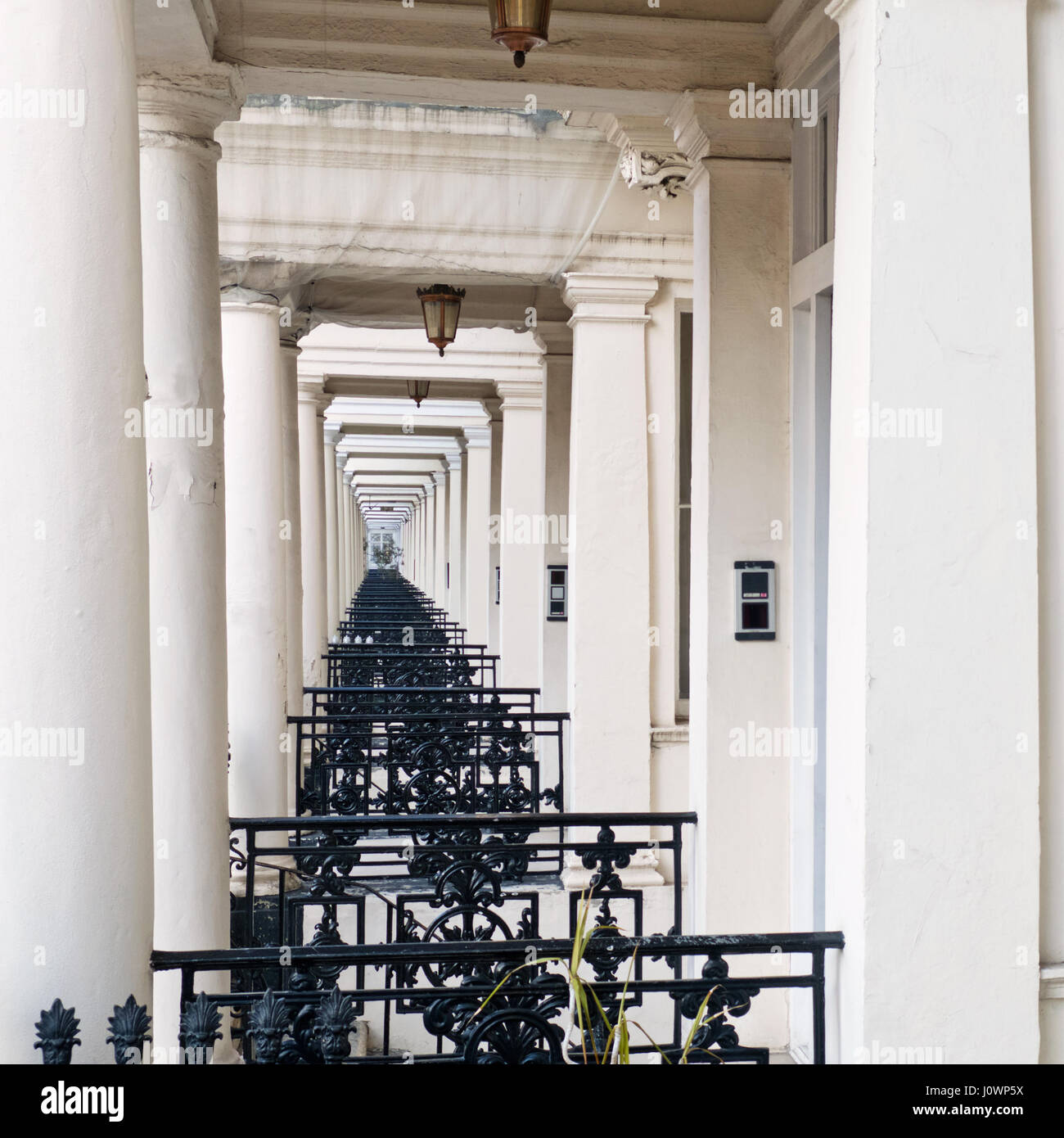 Side view through the porches of a terrace of Georgian housing in west central London - Stock Image