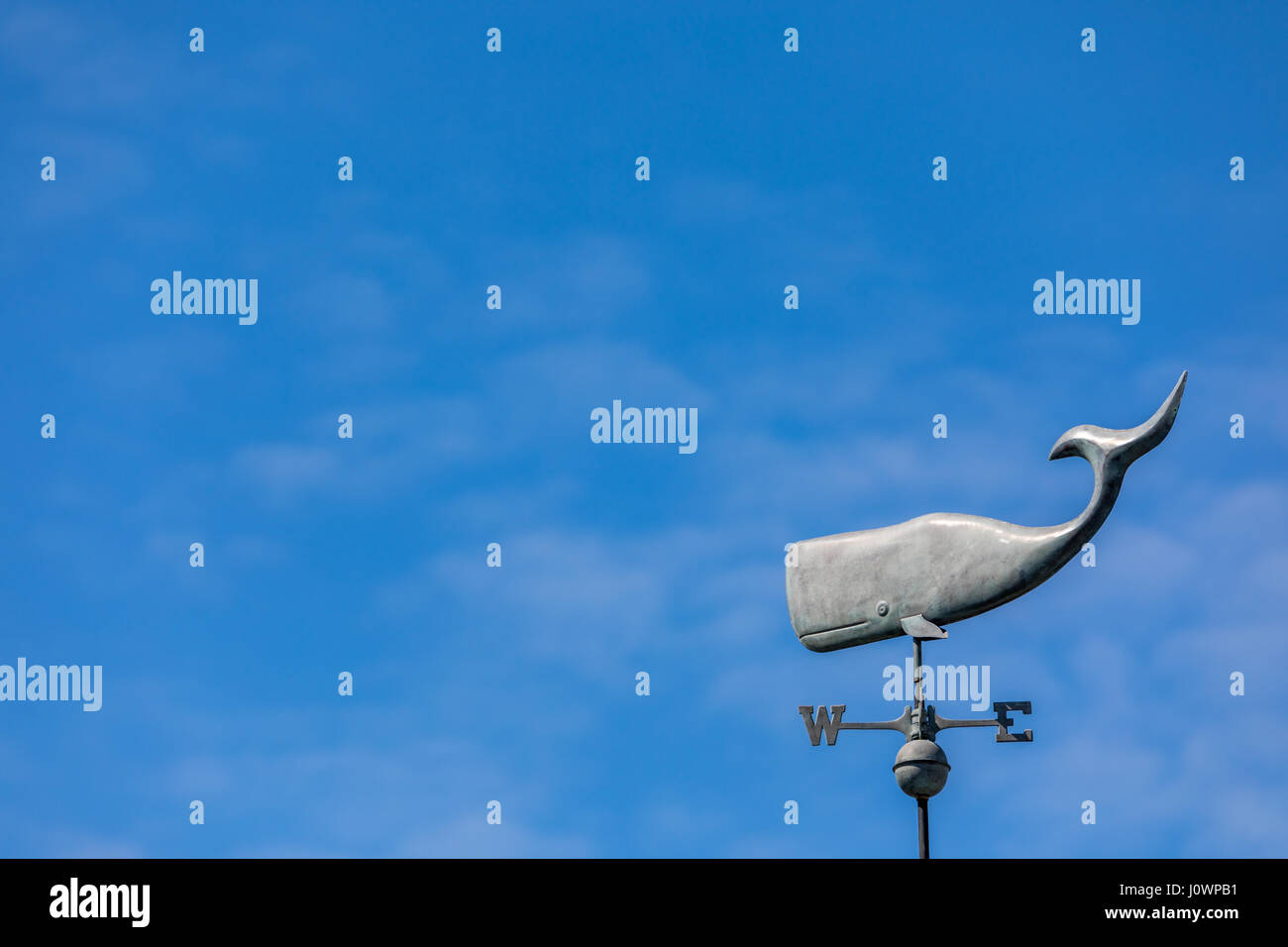 Metal whale weather vane in a blue sky - Stock Image