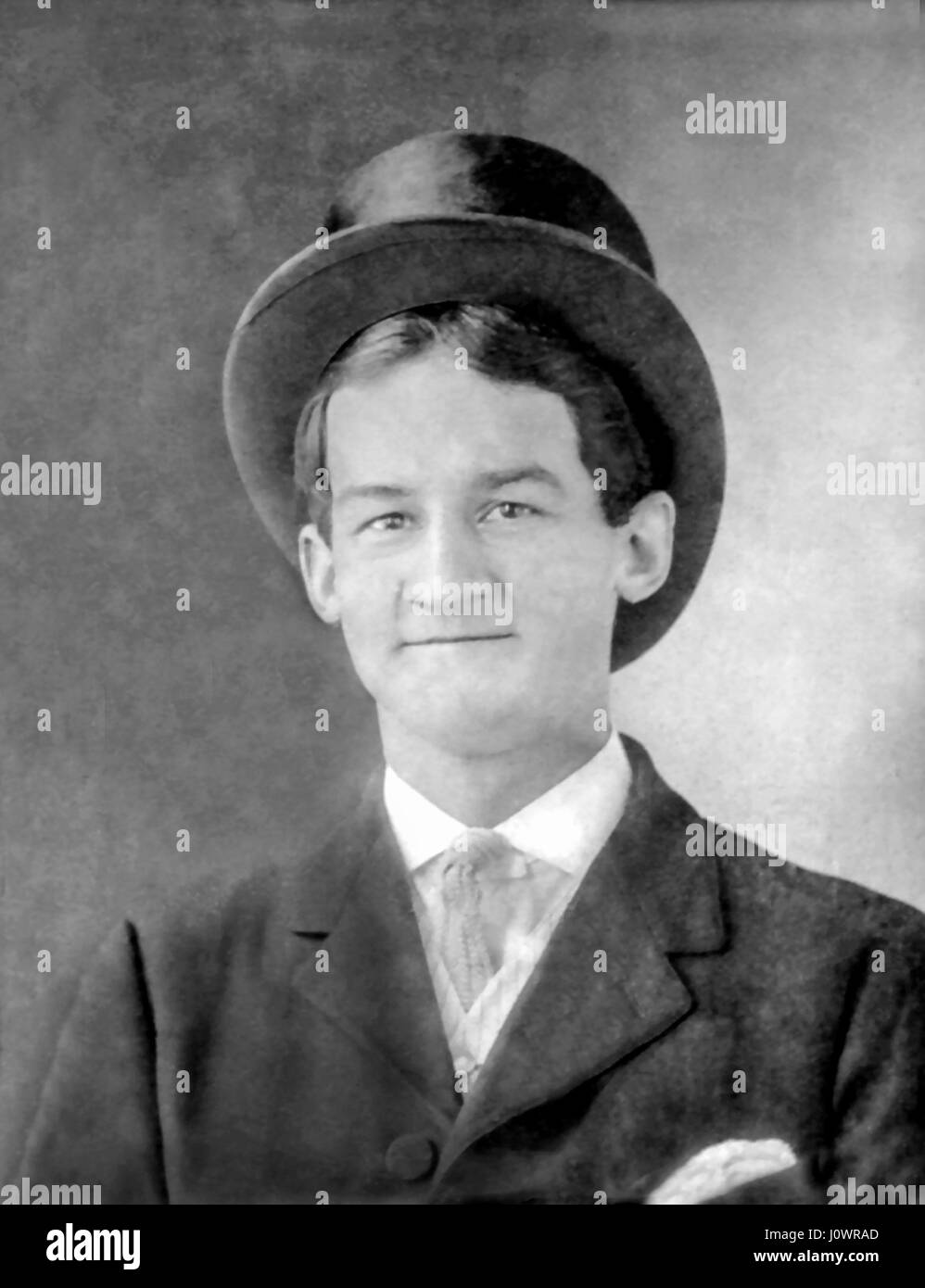 Vintage b&w portrait of a young man about eighteen-years old wearing a Victorian beaver top hat around 1915. - Stock Image