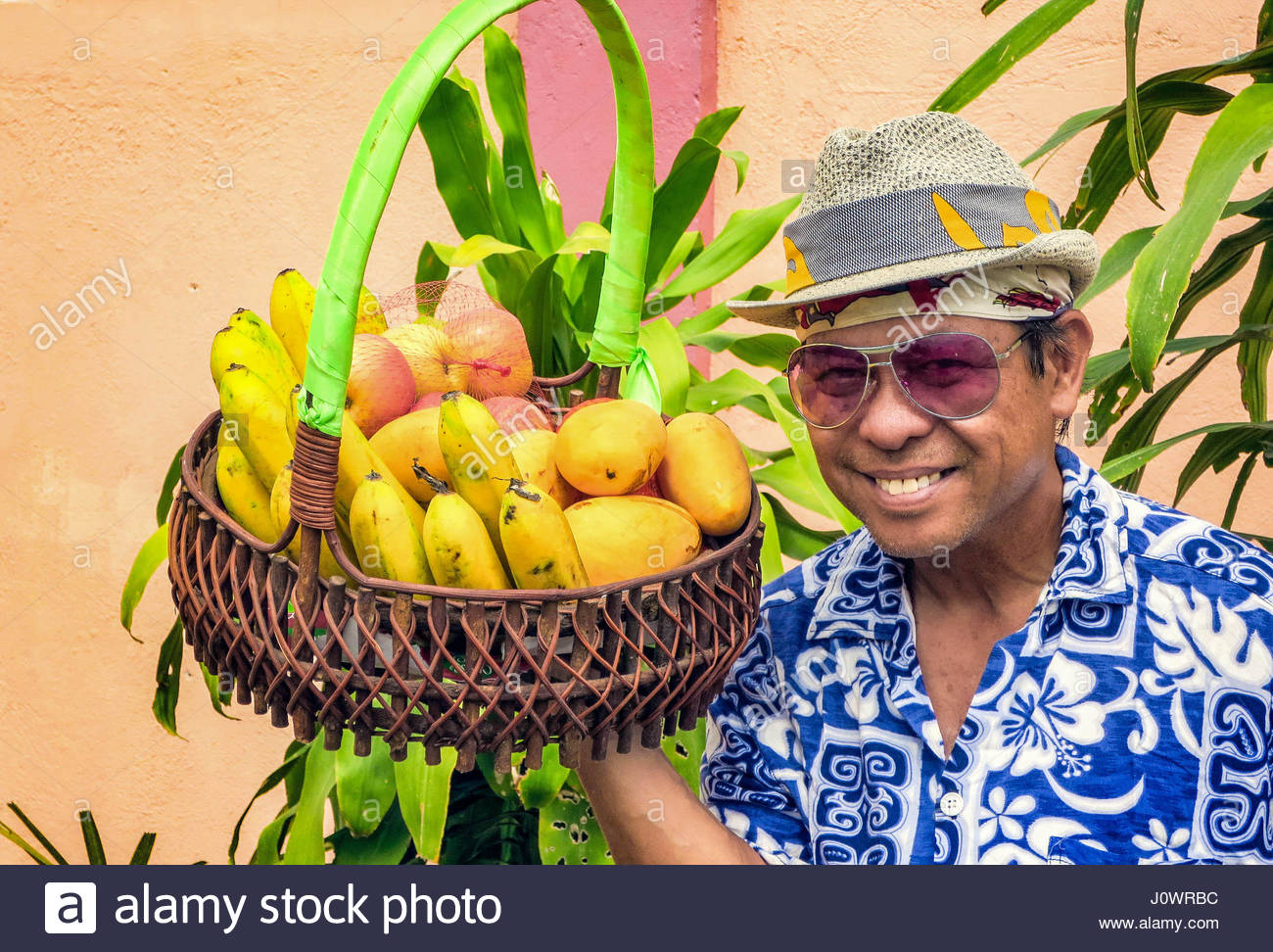 Portrait of a smiling Filipino man wearing a fedora hat, sunglasses and a flower shirt holding a basket of fresh - Stock Image