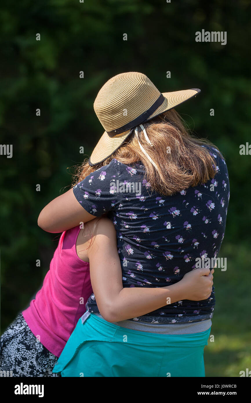 A mother wearing a straw hat and her daughter in a close embrase. - Stock Image