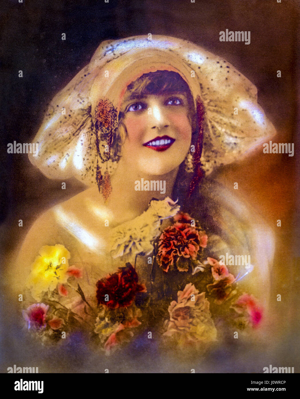 Hand-colored vintage portrait of a smiling 1920s era Flapper girl in her twenties wearing a wide brim cloche hat - Stock Image