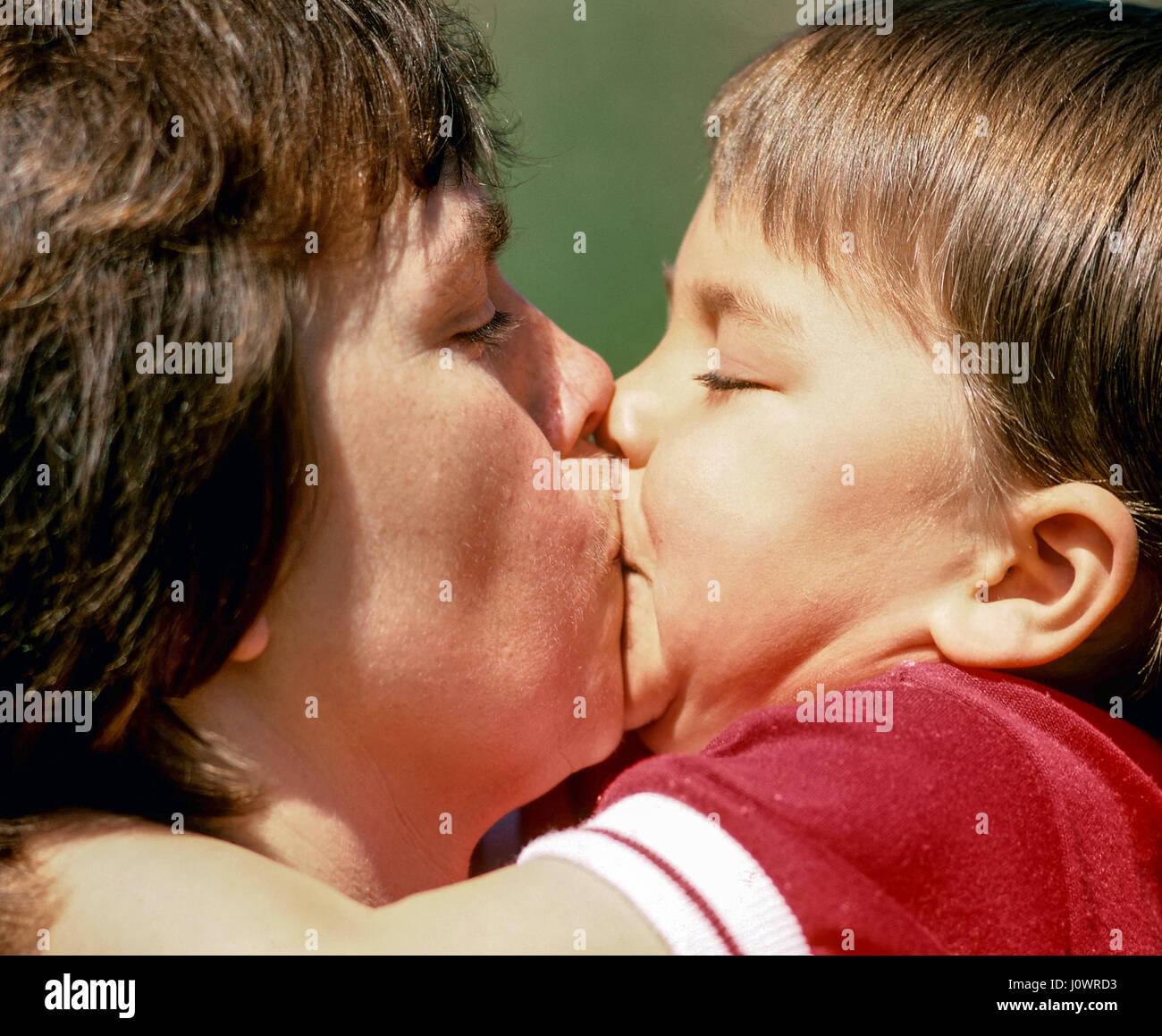 a cute three-year old boy plants a huge kiss on his mother in stock