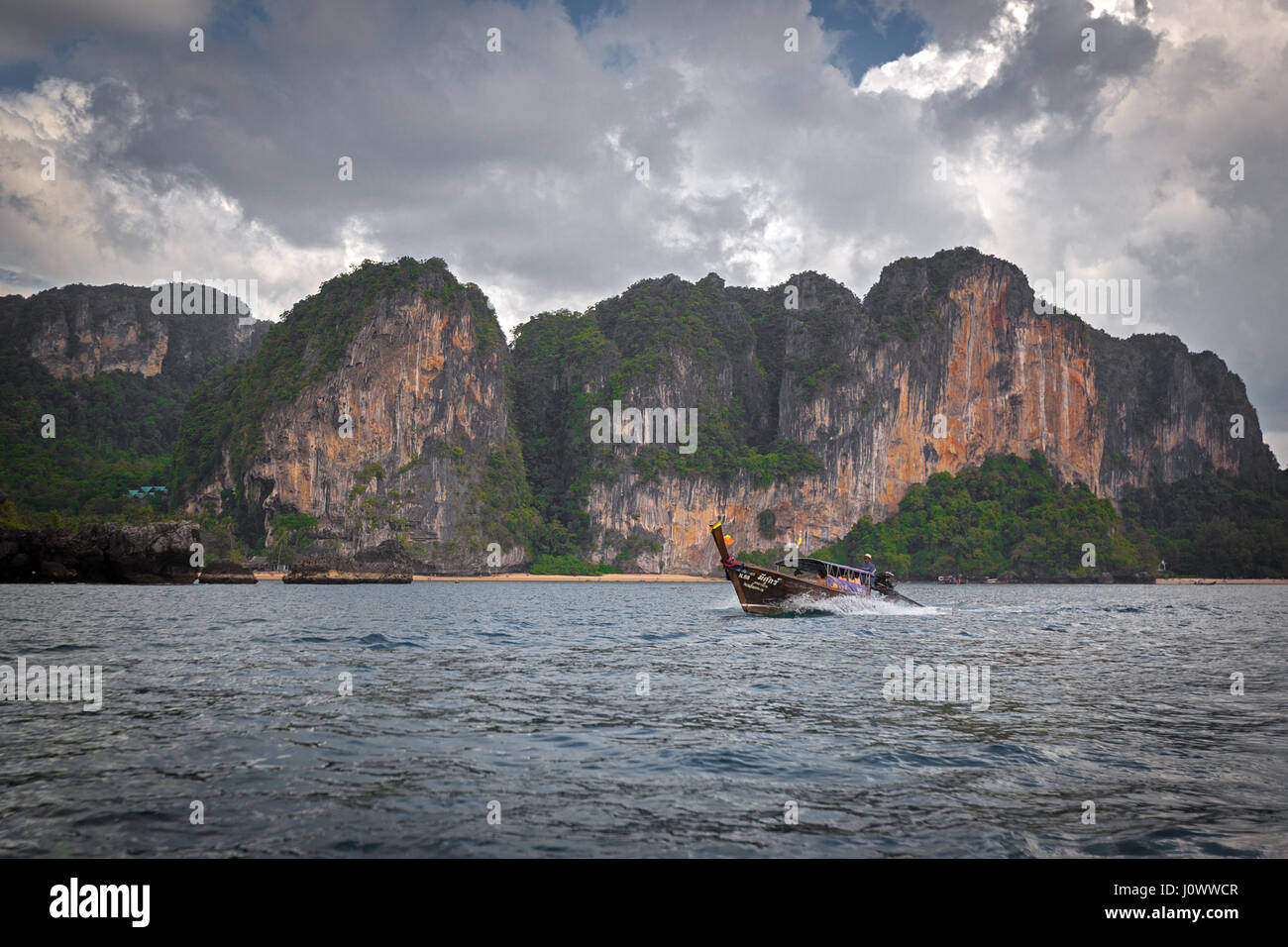 A long tail boat is heading back to Ao Nang from Railay Beach, Krabi Province, Thailand, Southeast Asia - Stock Image