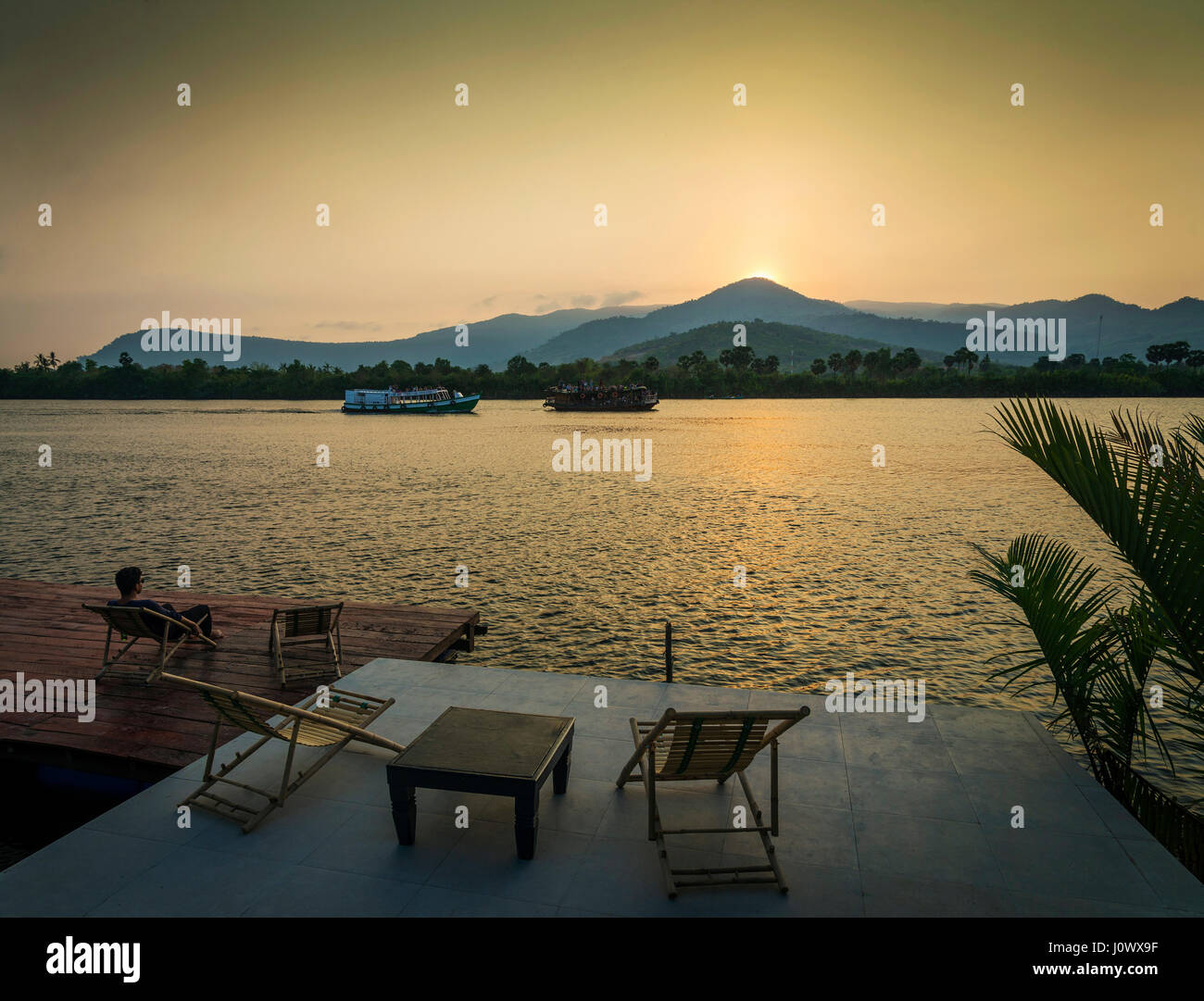 riverside sunset view in kampot cambodia asia with relaxing deck chairs and ferry boats - Stock Image
