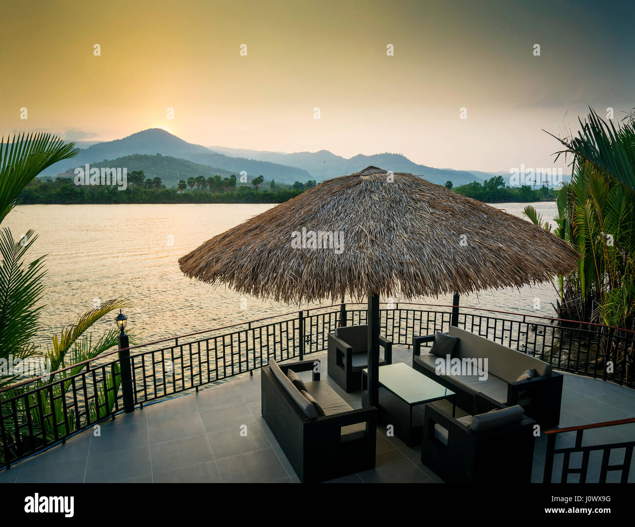 riverside sunset view in kampot cambodia asia with relaxing deck sofa chairs and table - Stock Image
