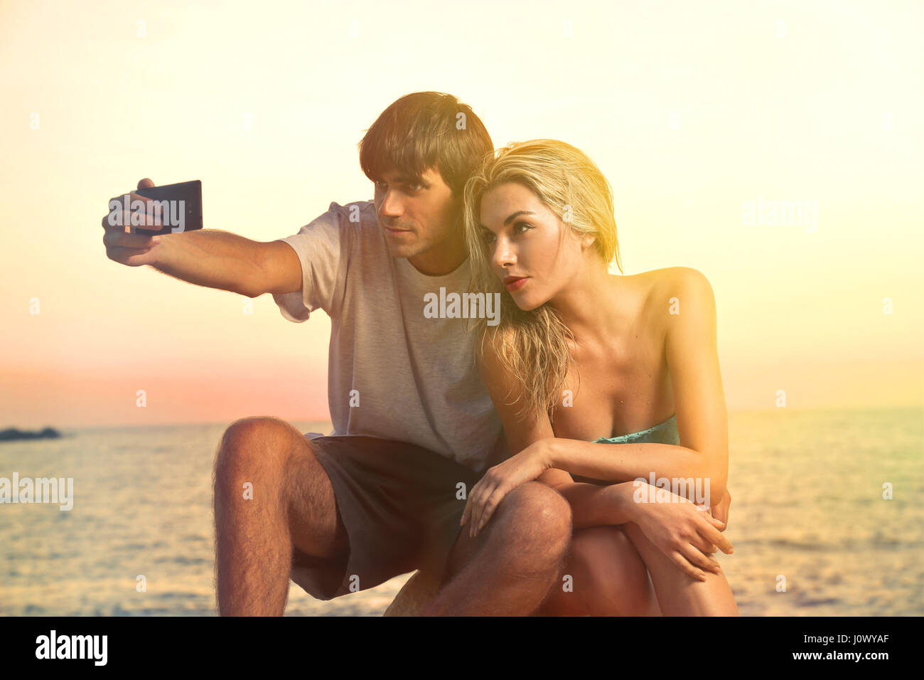 Couple taking a selfie at sunset - Stock Image