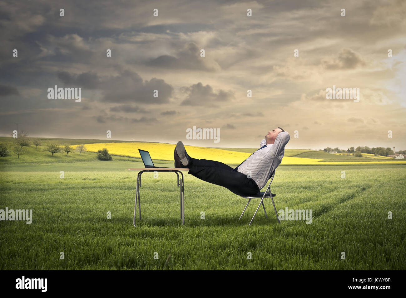 Businessman relaying on field - Stock Image