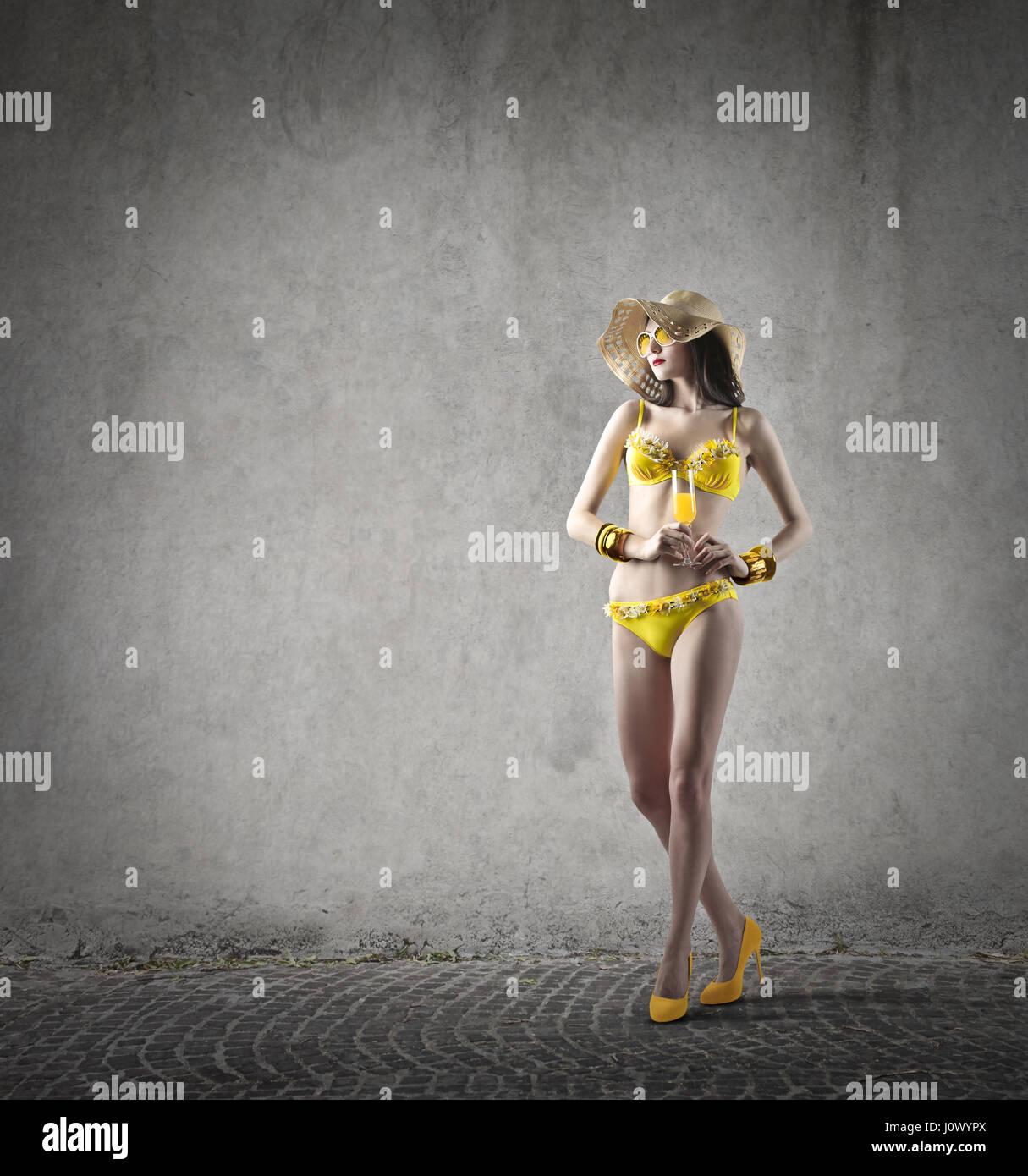 Woman in yellow bikini in empty room - Stock Image