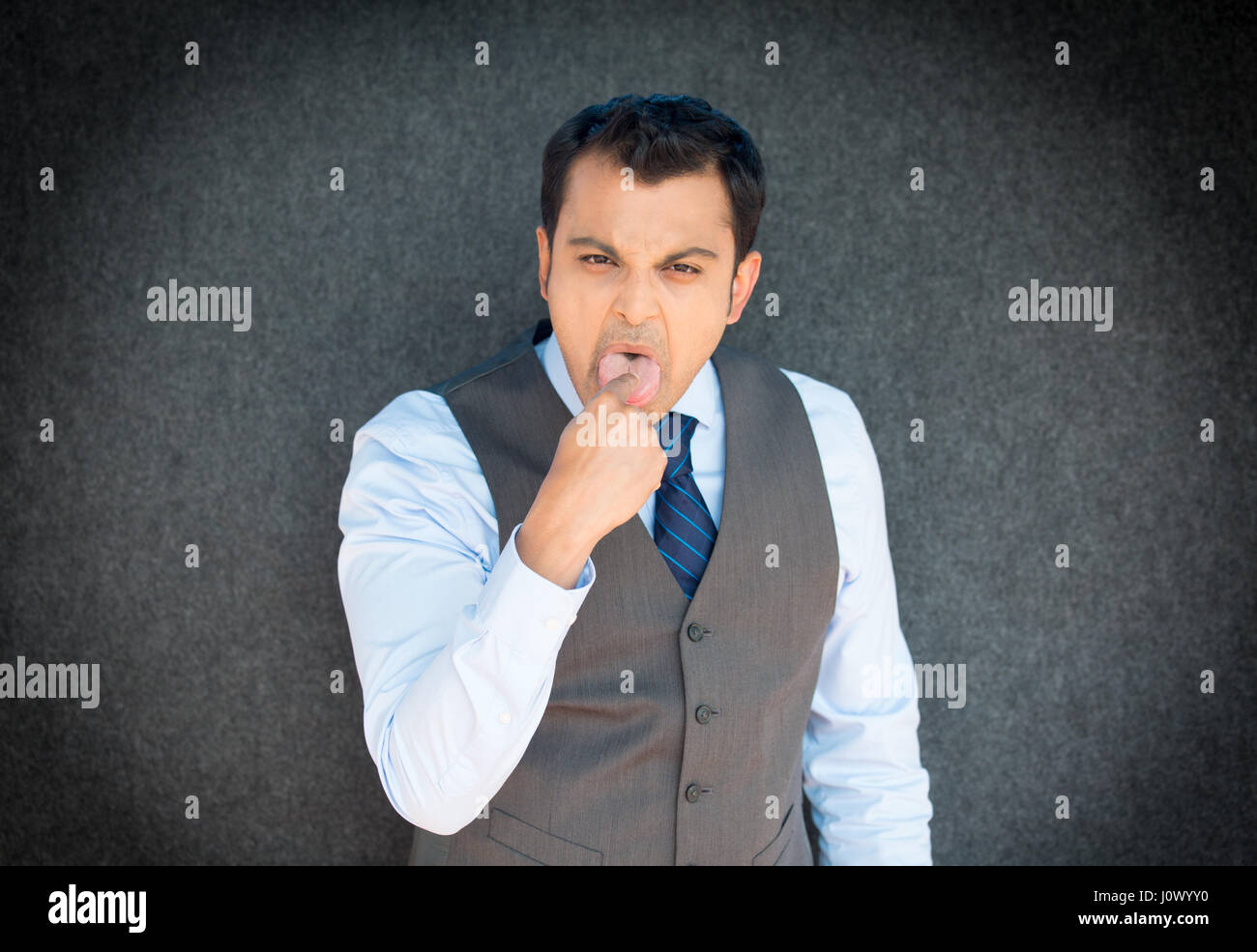 Closeup portrait of young angry, unhappy, business man, student, employee, finger in mouth, something sucks, gag, - Stock Image