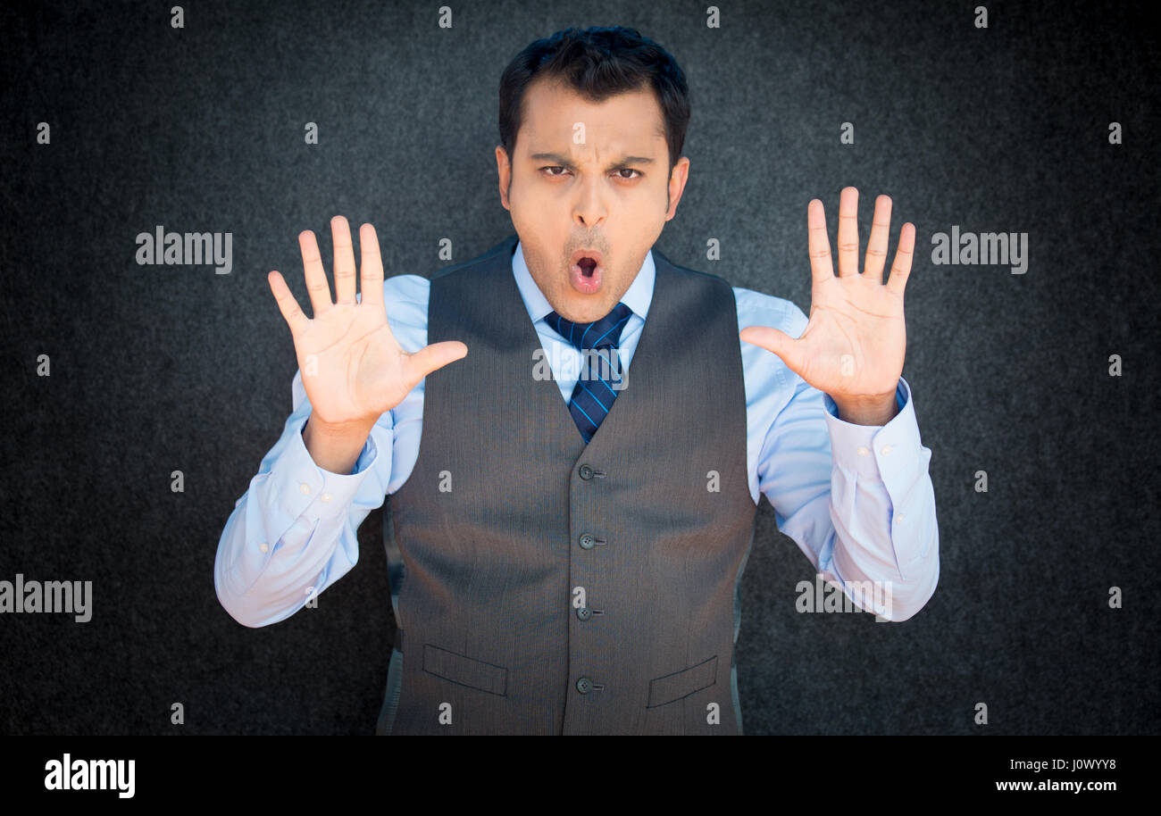 Closeup portrait of young, angry man in vest and blue tie, gesturing no with hands and saying stop with his mouth, - Stock Image