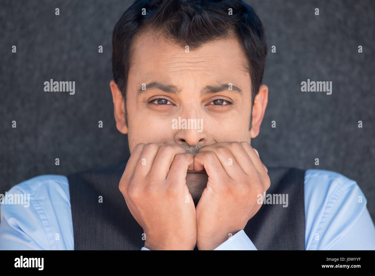 Closeup portrait, young unhappy man, biting his nails looking at you with craving for something, anxious, worried - Stock Image
