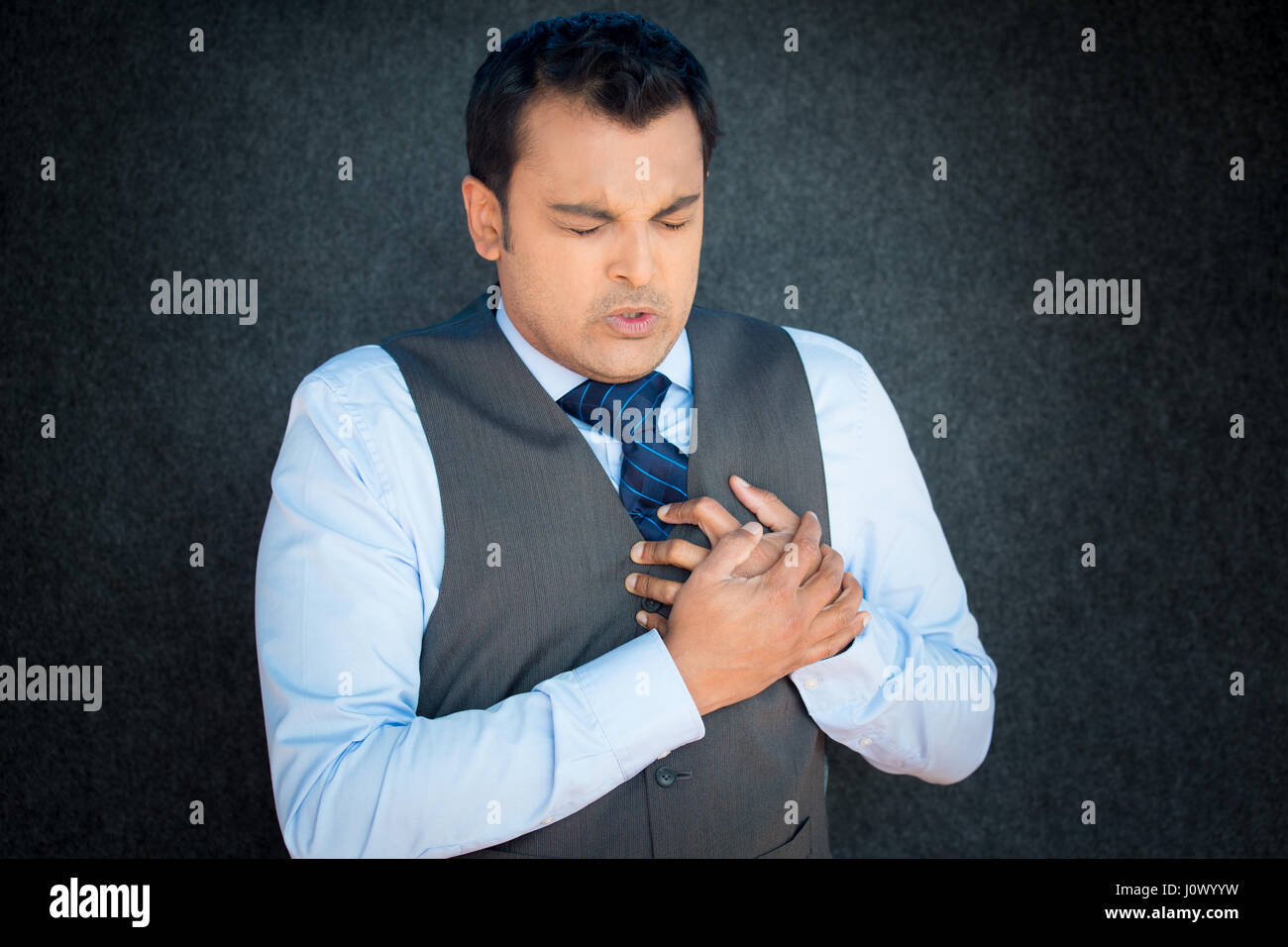 Closeup portrait, young gentleman in vest and blue tie, clutching chest tightly in severe substernal pain, grimace - Stock Image