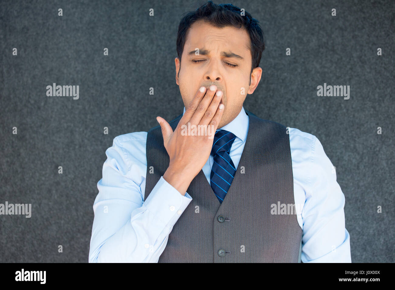 Closeup portrait of handsome young tired fatigued boss manager man placing hand on mouth yawning, eyes closed, isolated - Stock Image