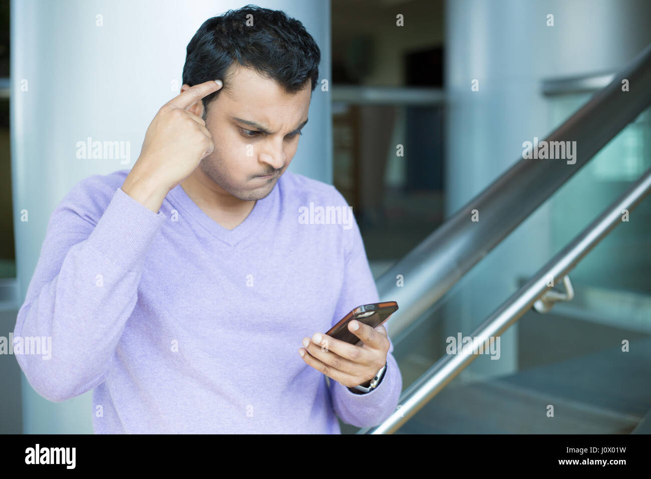 Closeup portrait, young man in purple sweater dumbfounded, flabbergasted about what he sees on cellphone, racking Stock Photo