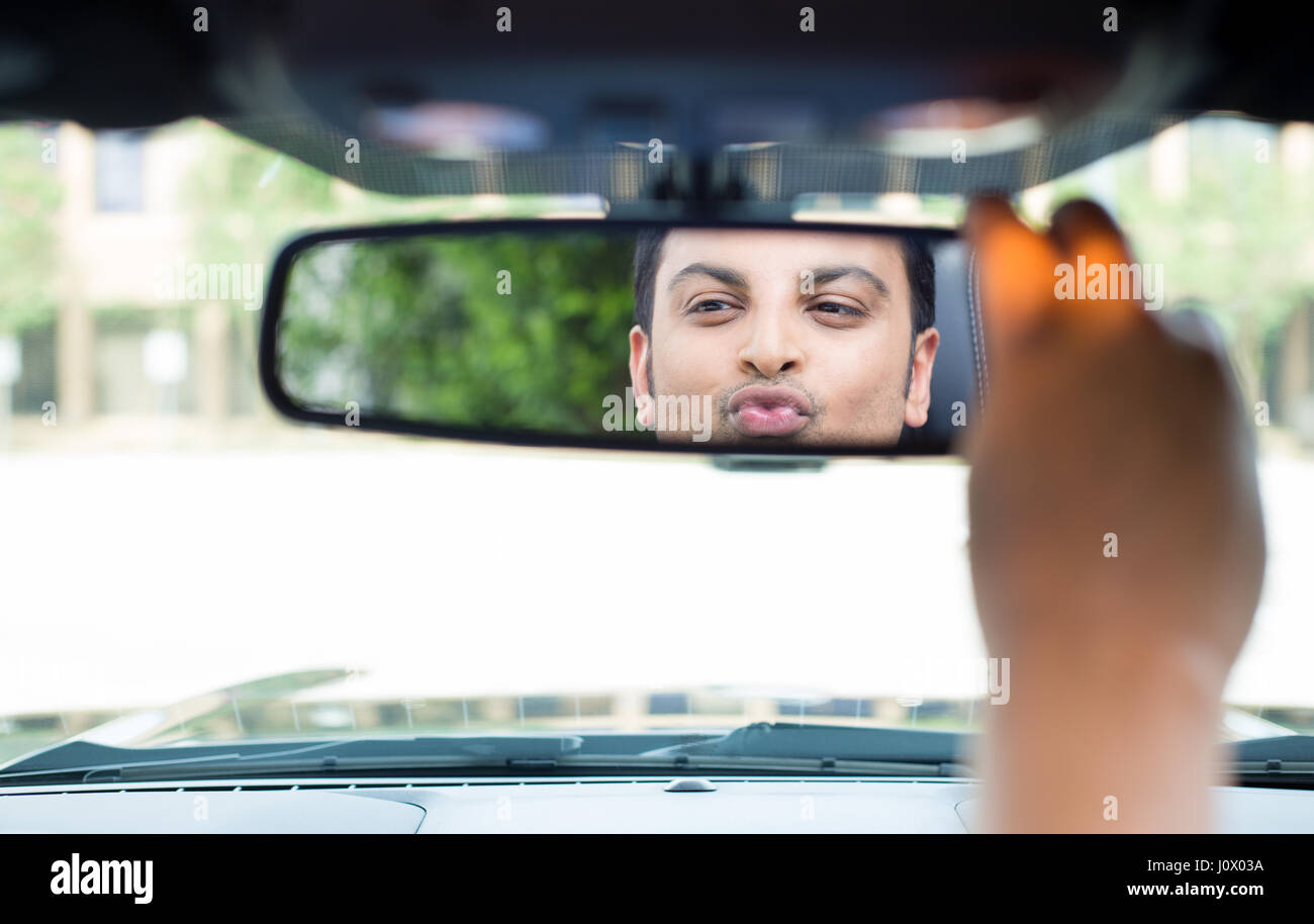 Closeup portrait, young handsome egotistical man in blue polo shirt looking at mirror reflection showing kisses - Stock Image