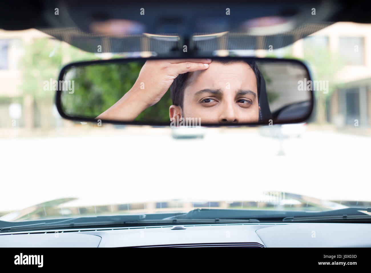 Closeup portrait, funny young man driver looking at rear view mirror looking at hair loss issues widow's peak or Stock Photo
