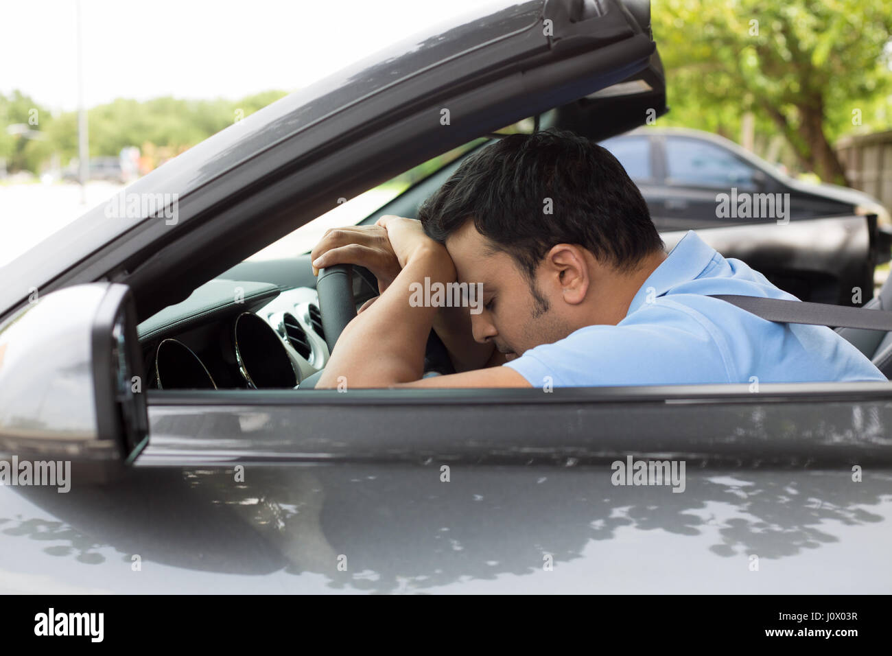 Closeup portrait tired young handsome man with short attention span, driving his car after long hours trip, trying - Stock Image