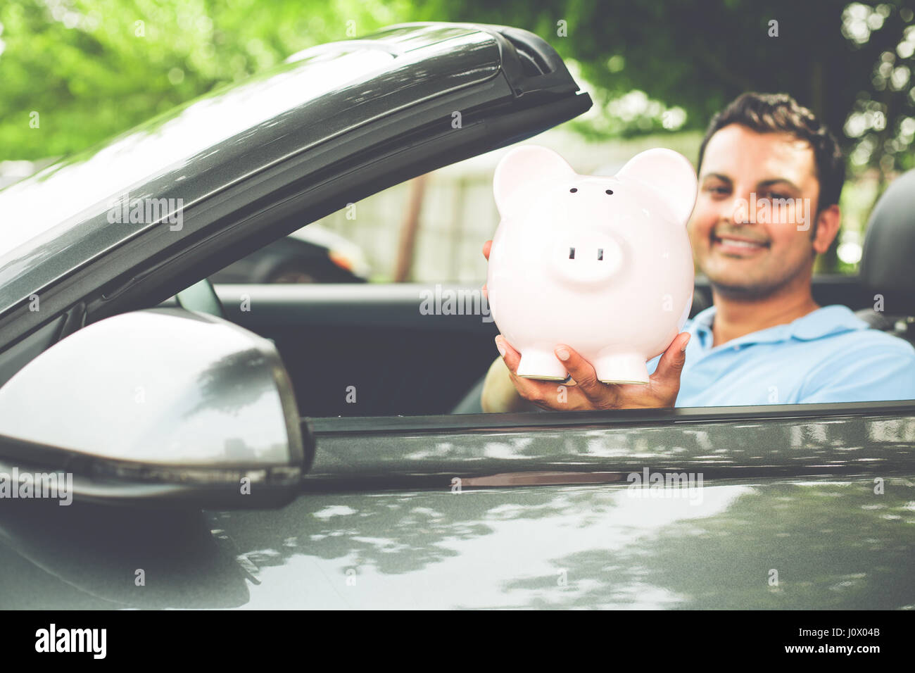 Closeup portrait, handsome young man in blue polo shirt showing pink piggy bank inside new sports car, isolated - Stock Image