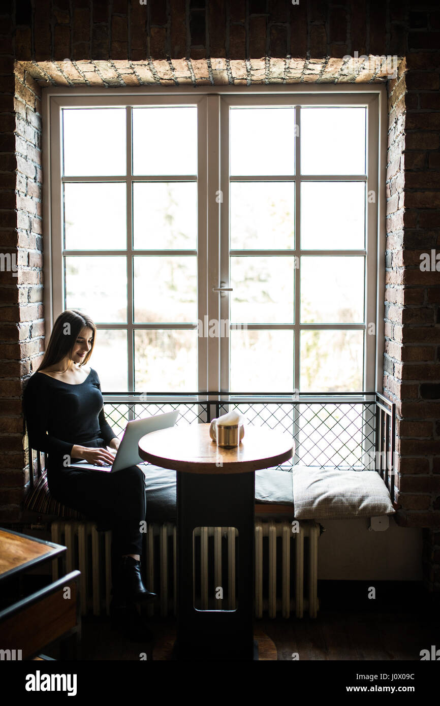 silhouette of young woman sitting at table in front of window and uses laptop. - Stock Image