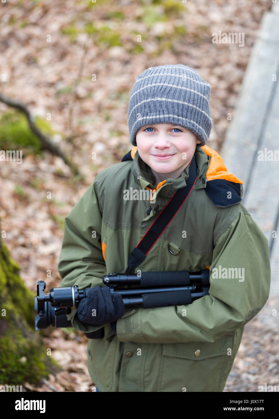 Handsome young boy with camera and tripod outdoors exploring a local nature reserve, Floda, Sweden  Model Release: - Stock Image