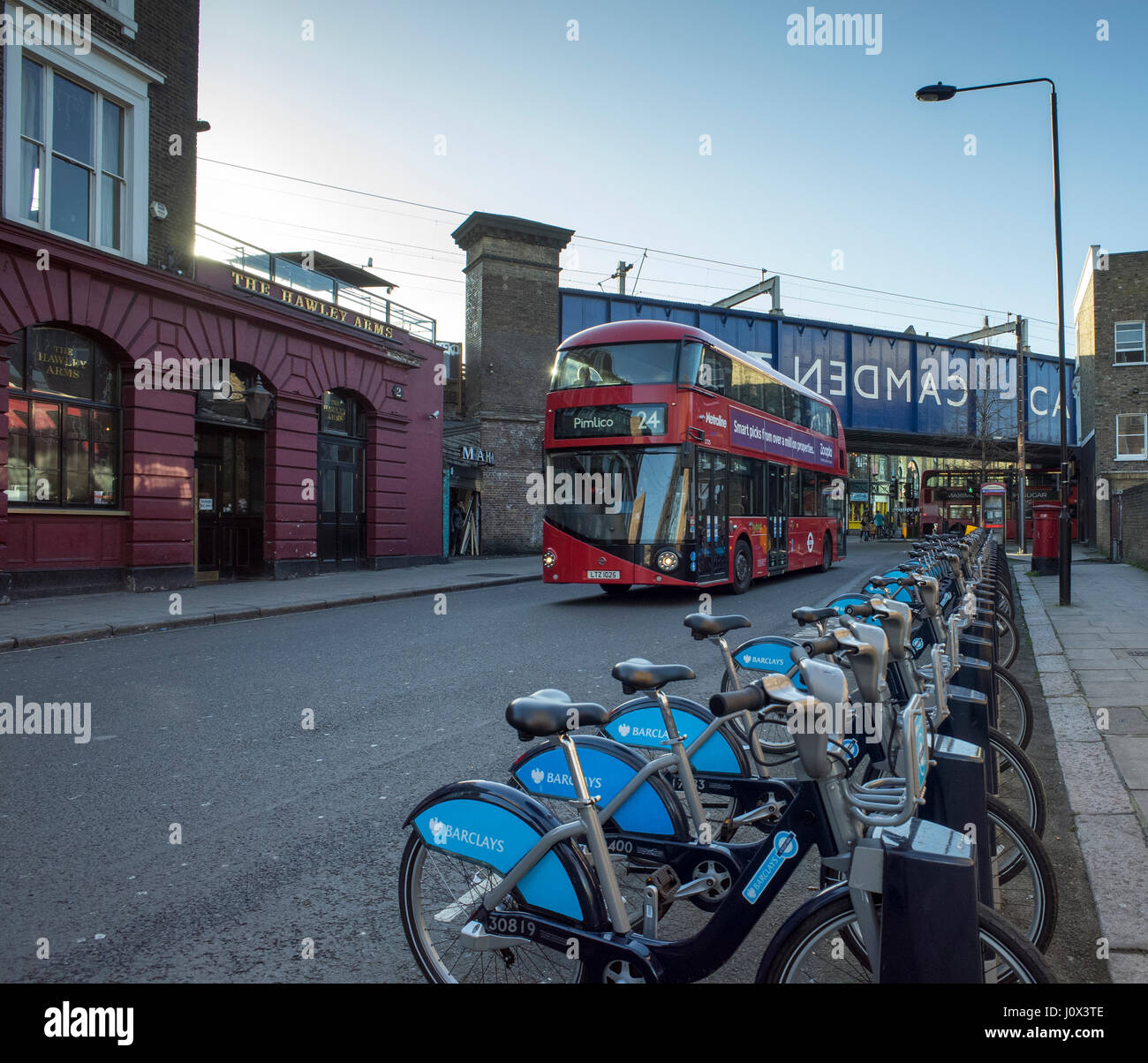 London new red Routemaster bus in Camden Town passing the Hawley Arms and a row of cycles for hire - Stock Image