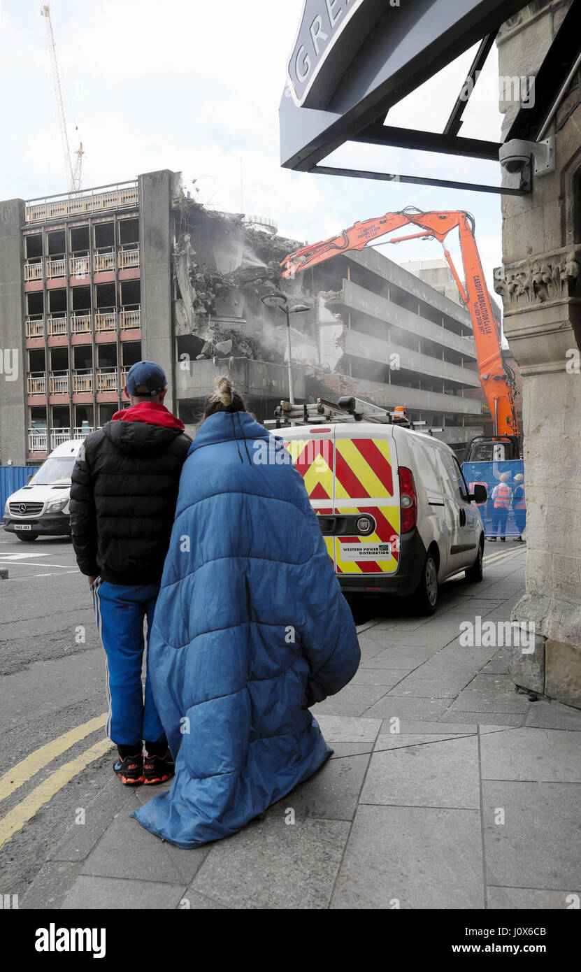 Homeless couple watch spec excavator demolition of derelict building on construction site at Wood Street car park Stock Photo