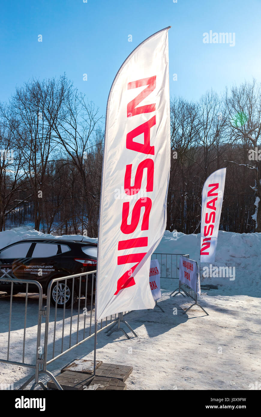 SAMARA, RUSSIA - FEBRUARY 14, 2016: Dealership flags Nissan over blue sky in sunny day. Nissan is a Japanese multinational Stock Photo
