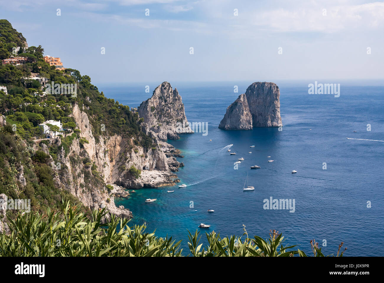 View of cliff coast of Capri Island with famous faraglioni rocks, Campania, Italy - Stock Image