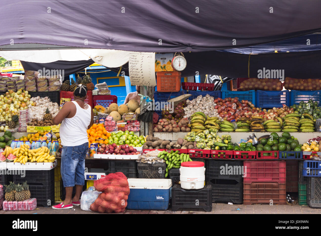 A vendor mans his produce stall in the floating market, Willemstad, Curacao - 11/27/2015 - Stock Image