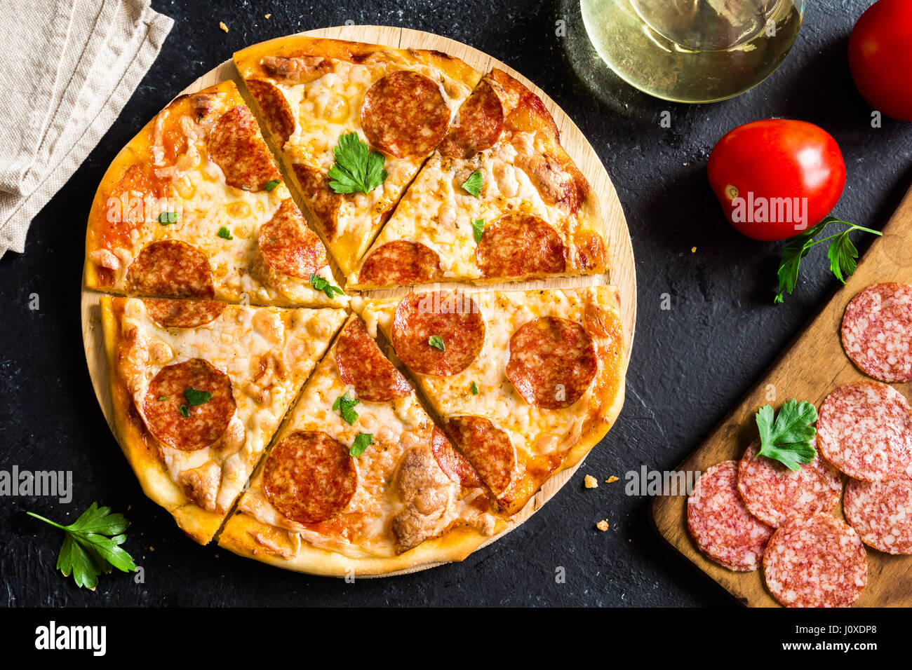 Pepperoni Pizza with ingredients - Fresh homemade pizza with pepperoni, cheese and tomato sauce and ingredients - Stock Image