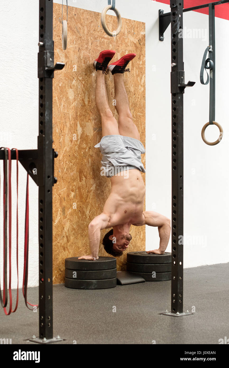 Angled view of strong man with bare chest doing handstand in gym - Stock Image