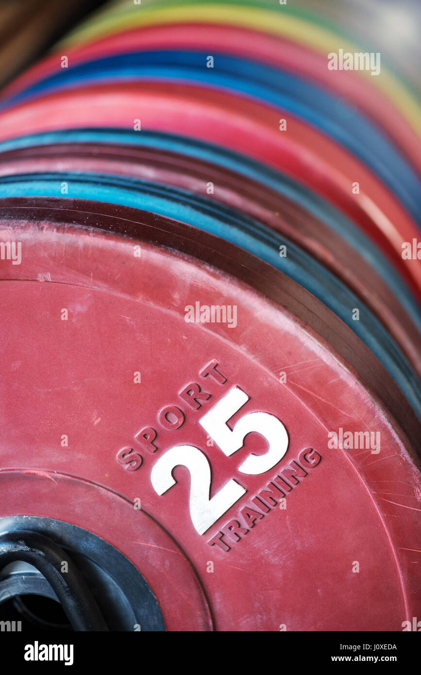 Close up on a stack of crossfit weights in a gym with focus to a red 25 kilogram weight in the foreground in a fitness - Stock Image