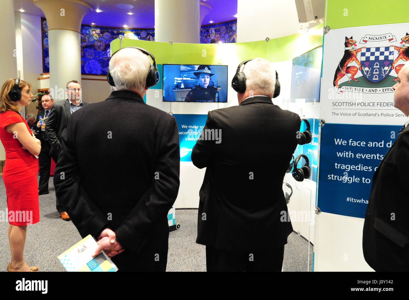 Scottish Conservative Party conference attendees on the Scottish Police Federation stand listen to sample police - Stock Image