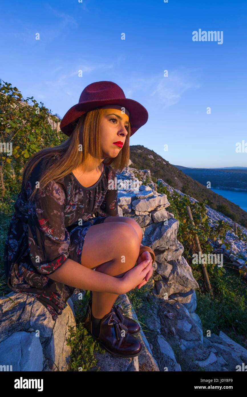 Young woman traditional vineyard serious watching sunset side-view sitting embrace embracing legs knees tucked legs Stock Photo