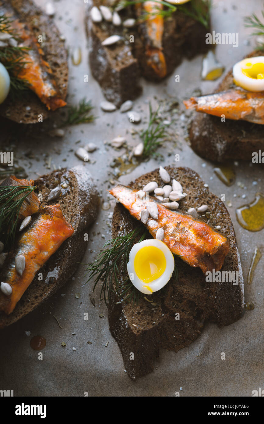 Sandwiches with sardines and quail eggs partial blur vertical - Stock Image