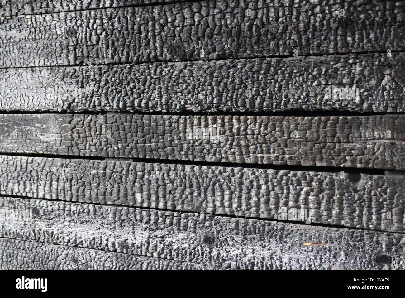 Charred wooden wall after  fire arson, Abstract black background - Stock Image
