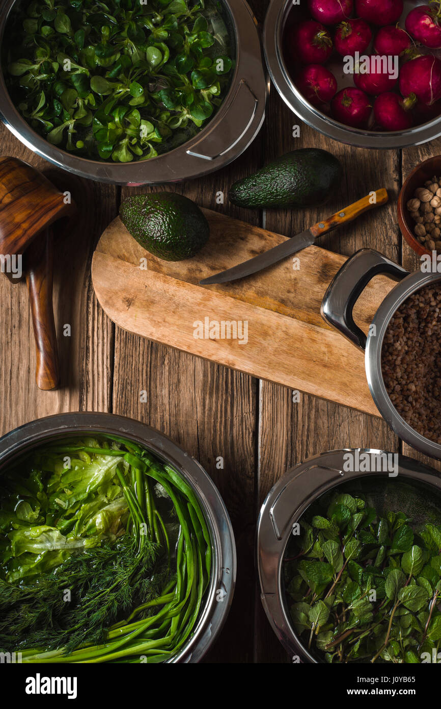 Avocado, green herbs in a bowl of water on the table vertical - Stock Image