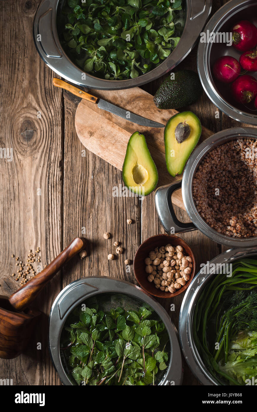 Halved avocado, greens in a bowl of water, radishes on the table vertical - Stock Image
