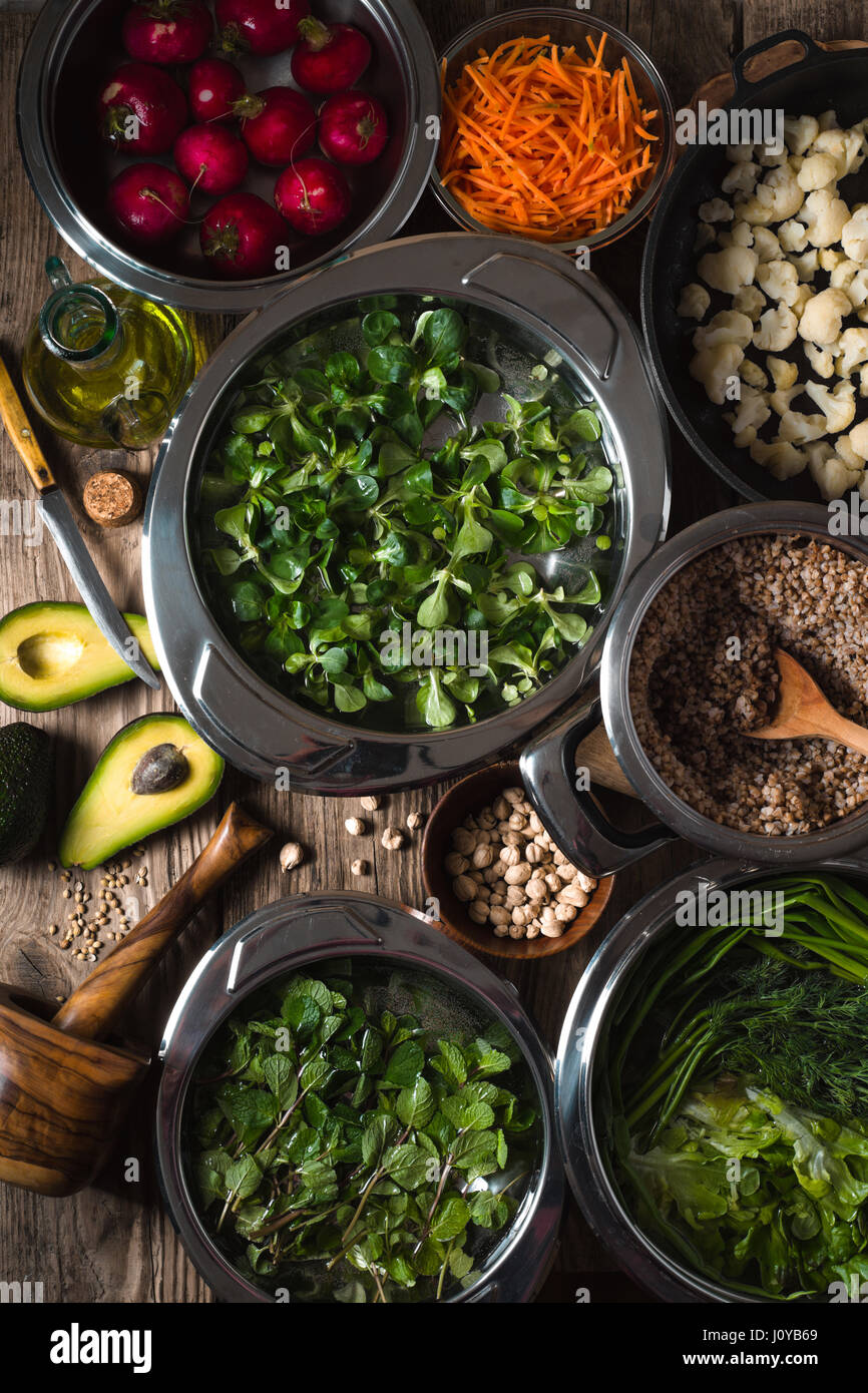 Vegetables, chickpeas, herbs in bowls in the water, half an avocado on the table vertical - Stock Image