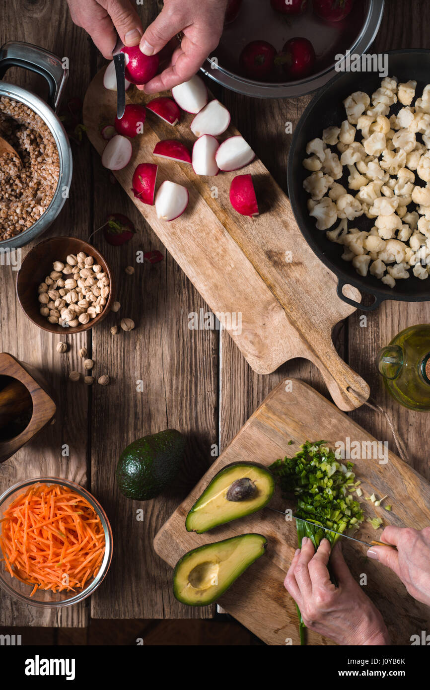Preparation Salad from radish, chickpea, avocado and carrot vertical - Stock Image