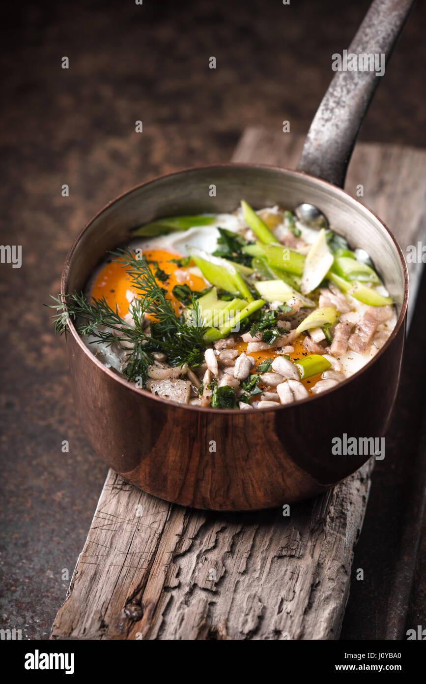 Scrambled eggs  with greens in the copper pot on the metal table  vertical - Stock Image