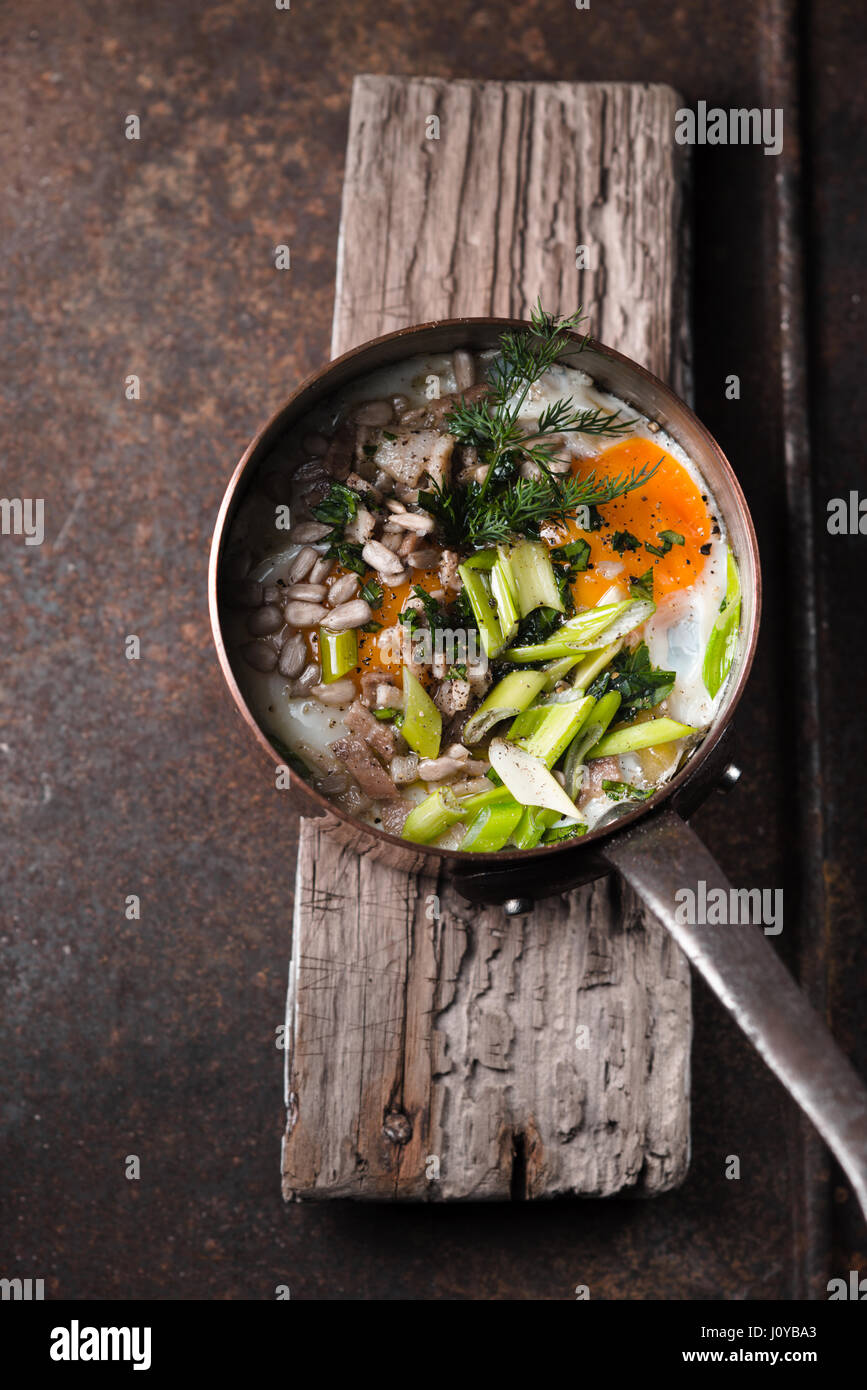 Scrambled eggs  with greens in the copper pot on the metal table  top view - Stock Image