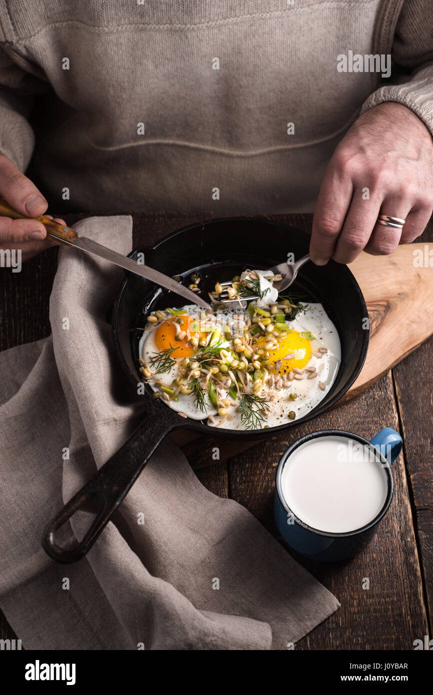 Eating scramble eggs on the wooden table vertical - Stock Image
