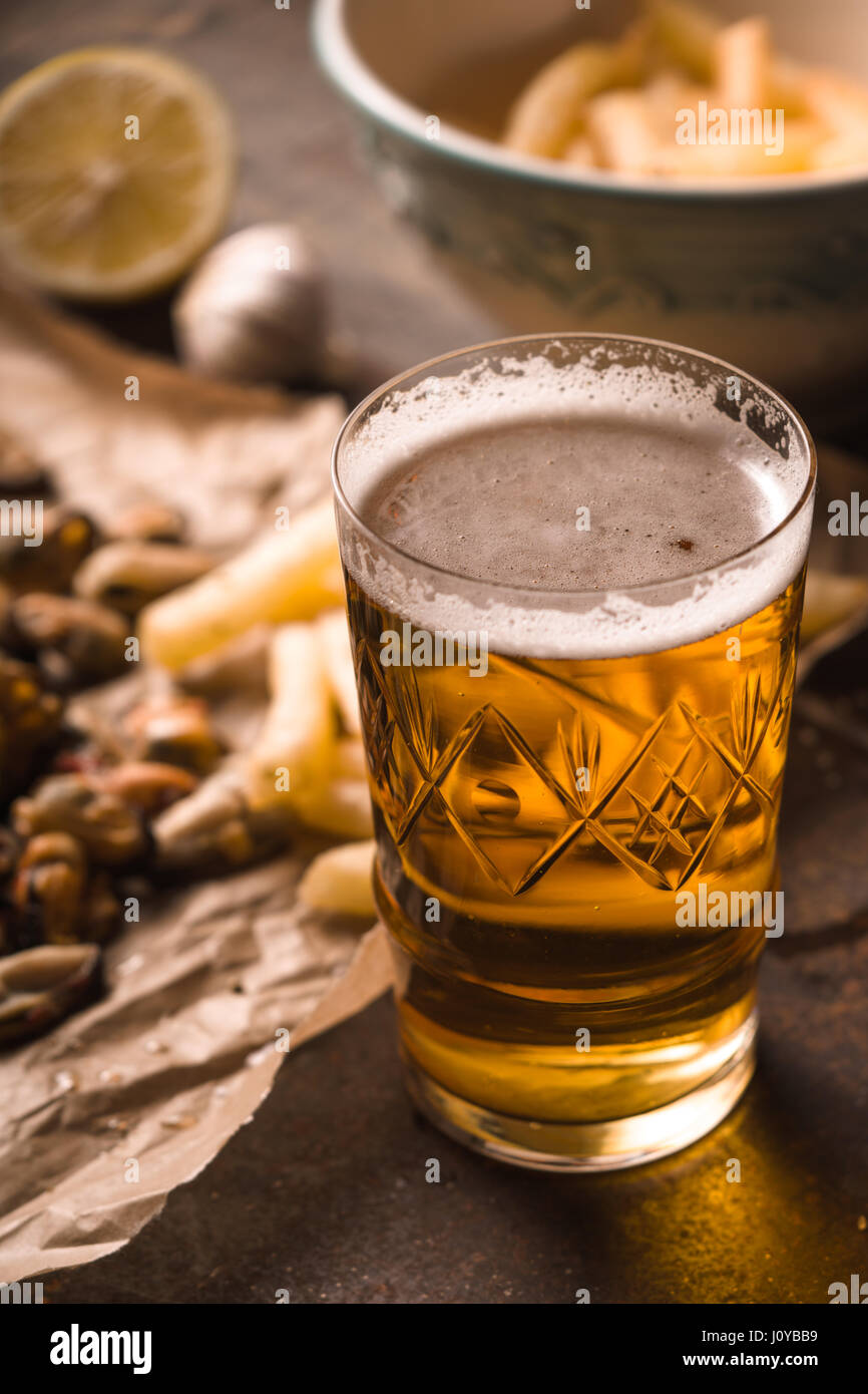 Glass of beer with blurred snack on the metal background - Stock Image